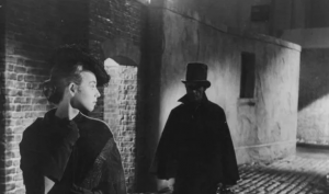 Woman followed by Jack the Ripper in black and white